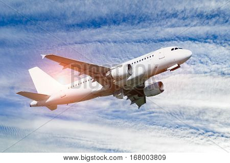 Airplane flying in the sky - travel background. Airplane closeup.Travel background with airplane flying in the colorful sunset sky. White flying airplane. Airplane in the sunlight. Closeup of flying airplane with blank livery