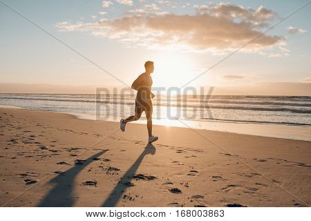 Runner Running In Morning Along The Beach