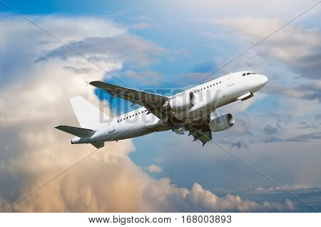 Airplane flying in the sky - travel background with flying airplane. Airplane closeup. Airplane with blank livery in the colorful sky - airplane in the flight. White airplane