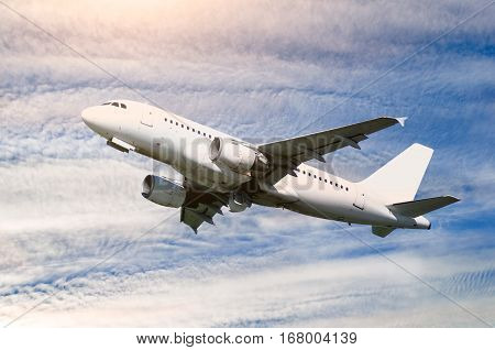 Airplane in the flight - travel background with airplane. Airplane closeup. Flying airplane with blank livery. Travel background with airplane in the sky. Commercial airplane in the flight. Closeup of airplane