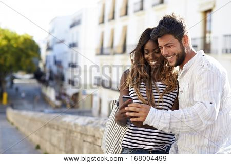Young adult couple looking at smartphone, Ibiza, Spain