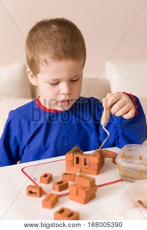 Portrait of cute preschool kid boy sitting at the table and making house of our small bricks. Creative child. Education and creativity concept. Activities with children at home.