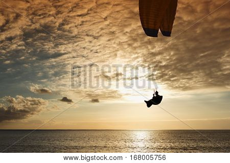 Silhouette of flying paraglider over the sea sunset