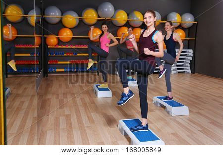 Young sporty women training with steppers in gym