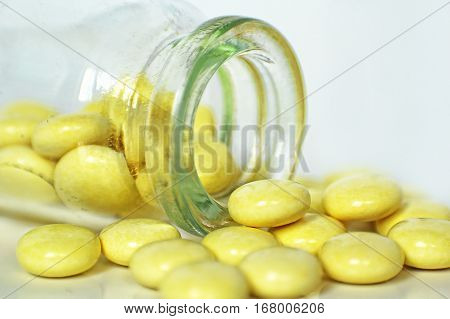 Yellow Medication Pills spilled out of Glass Drug Bottle on white background taken closeup.