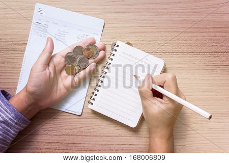 Coins On Hand With Bank Book Account Background, Hand Writing On Note Book