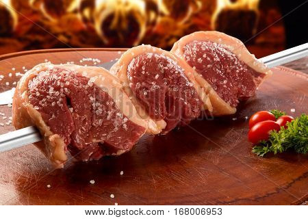 Brazilian Picanha. Raw meat. Background with fire