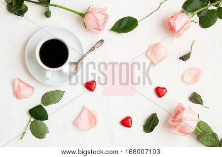 St Valentines day background - cup of coffee peach roses pink sheet of note heart shaped candies. St Valentines day still life for free space for St Valentines day message