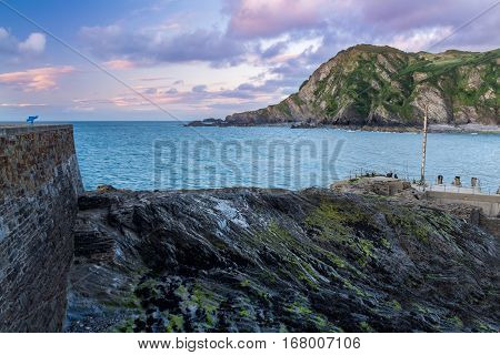 Ilfracombe Harbour. Calm sea. Evening. The sun sank behind the horizon. North Devon Coast. UK