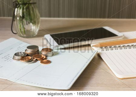 Coins Book Bank Account And Smartphone Or Mobile With Note Book Background