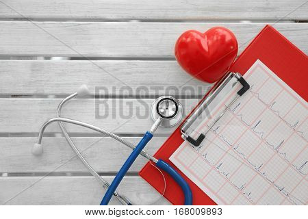 Stethoscope with red heart and paper electrocardiogram on table