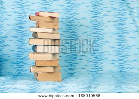 Old and used hardback books or text books on wooden table. Books and reading are essential for self improvement gaining knowledge and success in our careers business and personal lives. Copy space