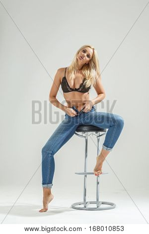 Beautiful sexy blonde in underwear and jeans sitting on a chair and posing, on a white background