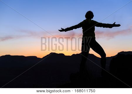 Woman hiking silhouette in mountains sunset happiness. Female hiker climber or trail runner with arms outstretched on mountain top looking at beautiful night sunset inspirational landscape.