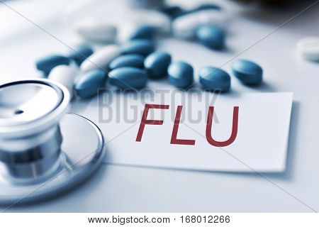 closeup of the desk of a doctors office with a stethoscope a bottle with pills and a piece of paper with the word flu