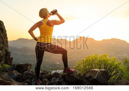 Woman hiking or running in mountains drinking water sunset on mountain top. Female hiker climber or trail runner with water bottle looking at beautiful night sunset inspirational landscape.