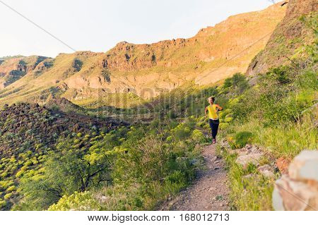 Young woman running on beautiful mountain trail at sunset summer day. Female runner training and working out jogging and exercising outdoors in nature Gran Canaria Canary Islands Spain.