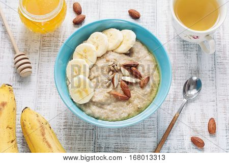 Bowl of oatmeal porridge with sliced banana, almonds, sunflower seeds and honey. Cup of green tea, jar of honey and ripe bananas on side.