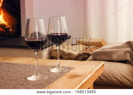 closeup of two glasses with red wine on table in living room with fireplace in the background