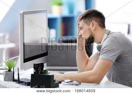 Handsome young programmer working at home