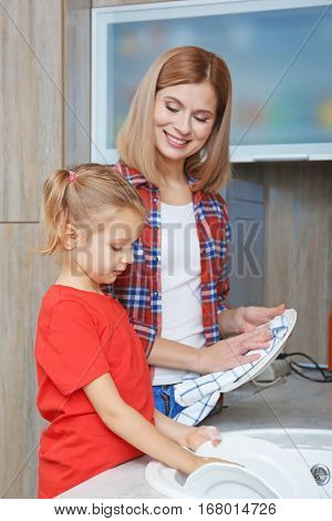 Little girl and her mother washing dishes at home
