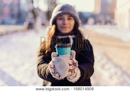 Beautiful Young Blonde Caucasian Woman In Winter Jacket, Knitted Beanie Hat , Holding A Takeaway Cup