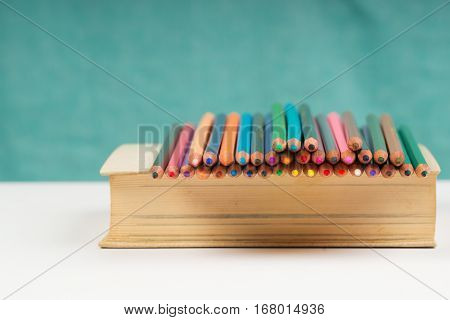 Multicolored pensils on the book. Back to school. Copy space. Top view.