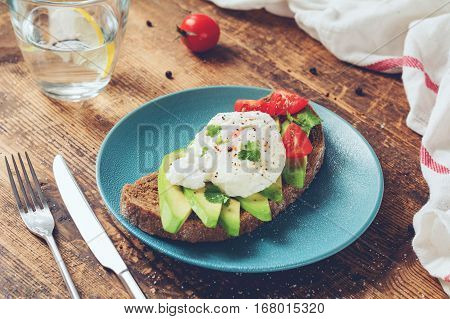 Healthy sandwich with poached egg and avocado served on a plate over wooden table. Toned image, selective focus