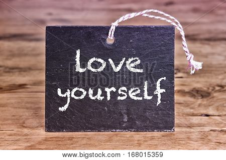 the words Love Yourself written on chalk borad on wooden table