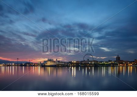 Wide angle view of Malaga harbor at dusk with silk water