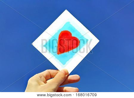 Hand holding a picture of a bright red heart against the blue sky