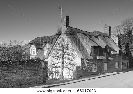 A monochrome image of a stone cottage with a thatched roof.