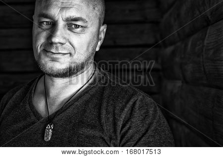 Bald mature man portrait. Black and white photo. Low-key style.