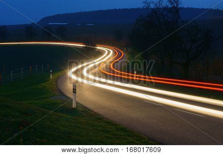 Car trails on the night road in the hilly countryside.