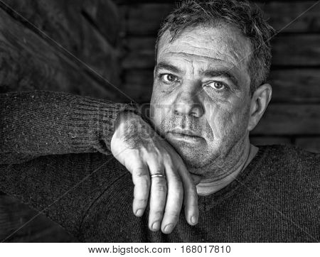 Sad mature man. His hand under his chin. Black and white portrait. Low-key style.