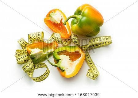 Multicolored bell pepper with measuring tape isolated on white background. Top view.
