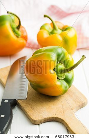 Multicolored bell pepper with knife on cutting board.