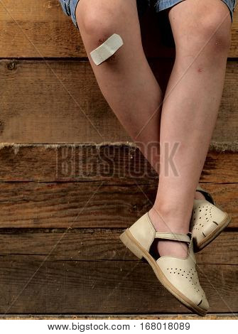 feet of a child with a sore patch on his knee and summer on wood background