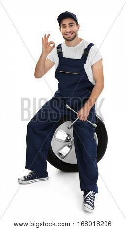 Young mechanic in uniform with spanner and wheel on white background