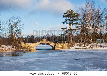 View of the humpback bridge at sunny day in January. Gatchina Palace and Park Russia
