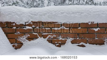 Red brick wall covered by snow