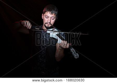 Young bearded violinist playing on electric violin white on a black background