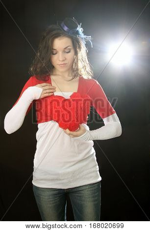 Girl with red soft heart on a black background in the light of soffit