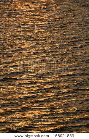 Sea waves, low-lit by the setting sun
