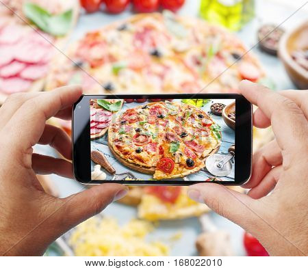 Taking photo of pizza by smartphone. Closeup view of  process. File contains clipping paths for smartphone and it's picture.