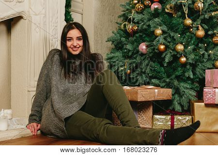 Beautiful young brunette girl sitting on the floor near a Christmas tree. Studio horizontal photo