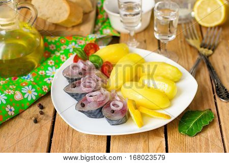 Pickled bismarck herring with onions and potatoes served with vodka