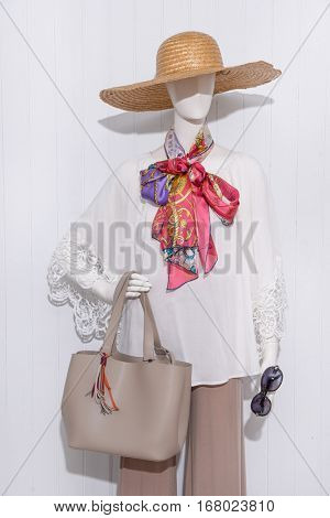 female clothing with hat and scarf, bag, sunglasses on mannequin-wooden background  female clothing with hat and scarf, bag, sunglasses on mannequin-wooden background