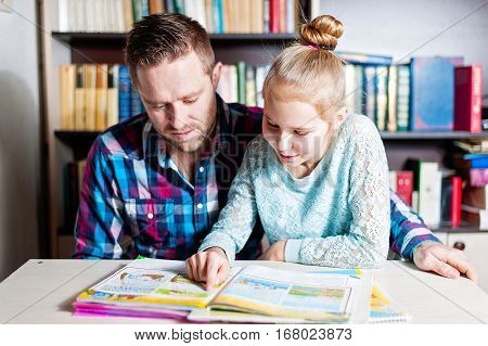 Young Father Helping Her Daughter With School Project At Home