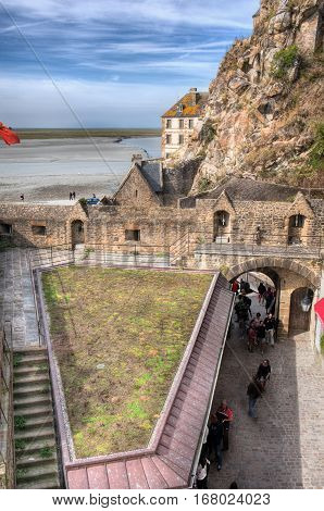 View from Top tower of coastal stone fortifications to entrance in Mont-Saint-Michel, Normandi France
